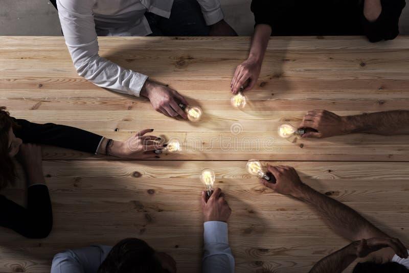 Teamwork- och id?kl?ckningbegrepp med aff?rsm?n som delar en id? med en lampa Begrepp av starten royaltyfri bild