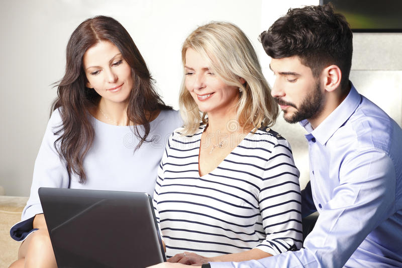 Teamwork at office. Portrait of executive busiensswoman sitting at office with laptop while business peope sitting next to her. Business team working together on royalty free stock photo