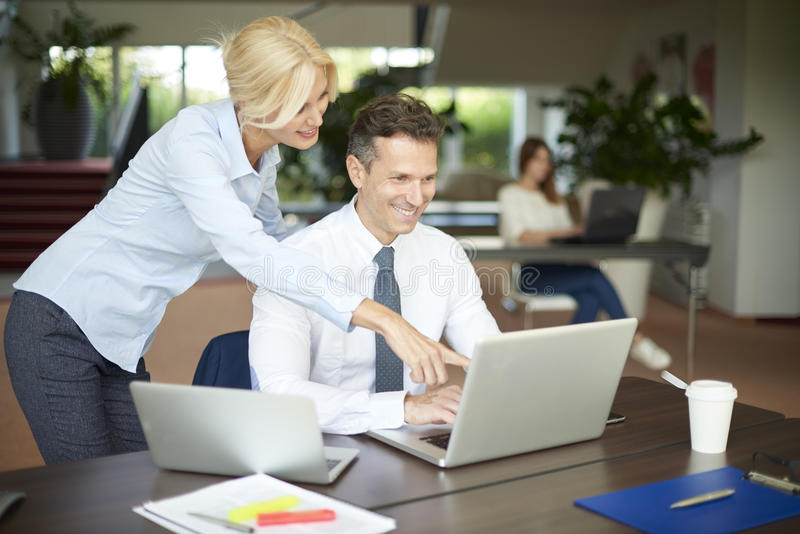 Teamwork at office. Shot of a middle aged financier advisor sitting in front of laptop and consulting with female assistant while working together stock photography