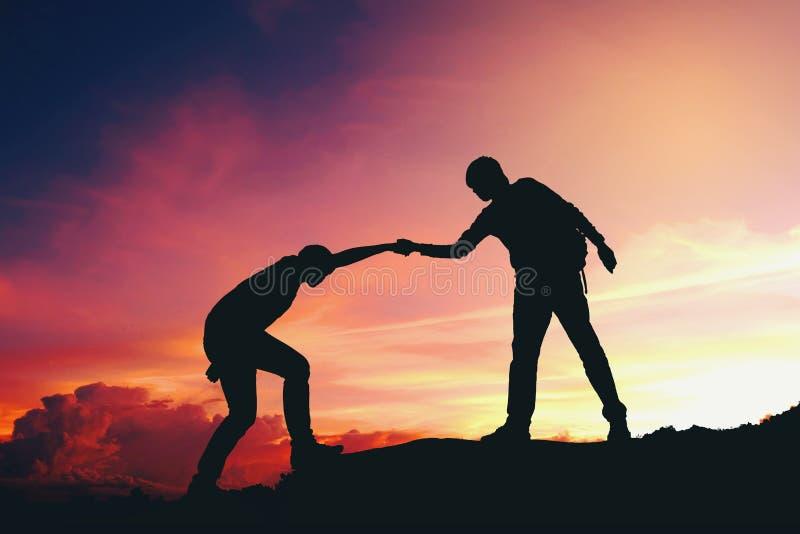 Teamwork-Paare, die wandernd Schattenbild auf Berg helfen stockfotografie