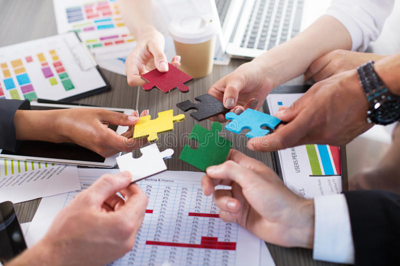 Teamwork of partners. Concept of integration and startup with puzzle pieces royalty free stock image