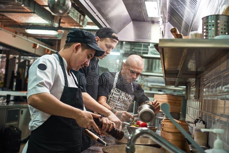 Teamwork Restaurangkock och hans två assistenter i förkläden som lagar mat en ny maträtt i ett modernt kök fotografering för bildbyråer