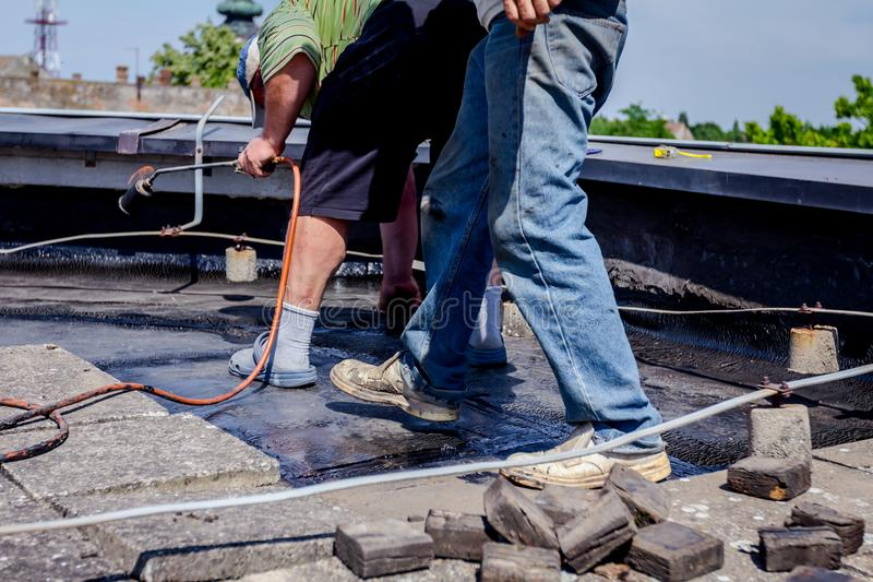 Teamwork at roofing installation resin. Heating and melting of bitumen surface by flame from gas torch. Worker adjusts bituminous cover for roofing felt, smears stock photography