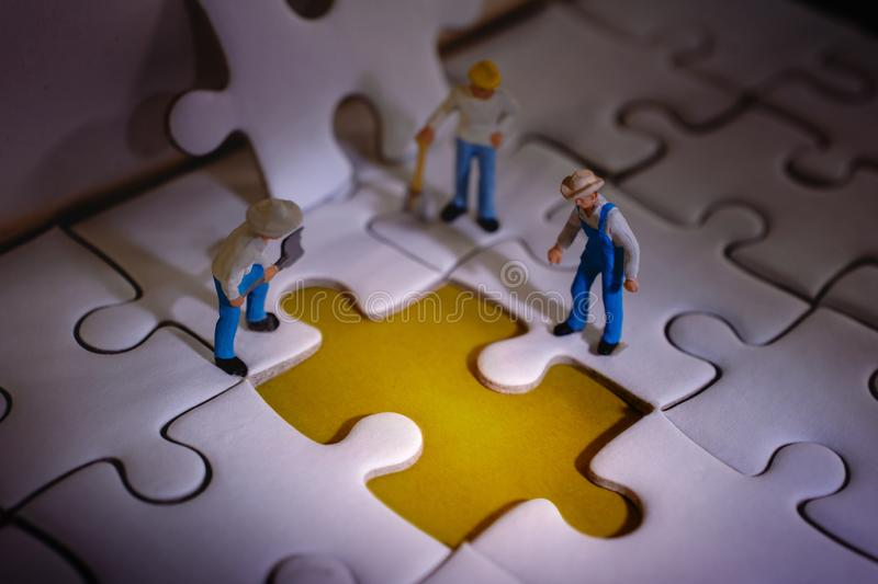Teamwork and Solving Problem Concept. Group of Miniature Worker Men Found Something Wrong on the Work Process a Piece of Jigsaw stock photo