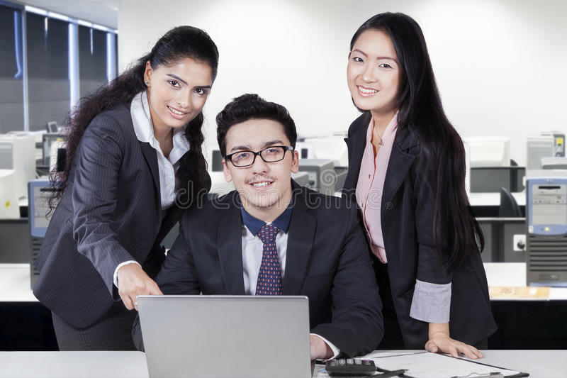 Teamwork som diskuterar med bärbara datorn på arbetsplatsen arkivfoto