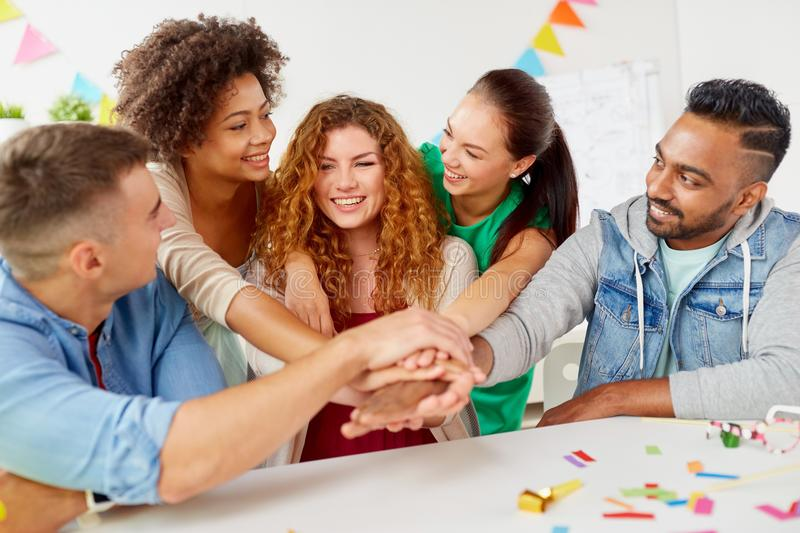 Happy business team at office party holding hands. Teamwork, success and celebration concept - happy business team holding hands together at office corporate stock photos