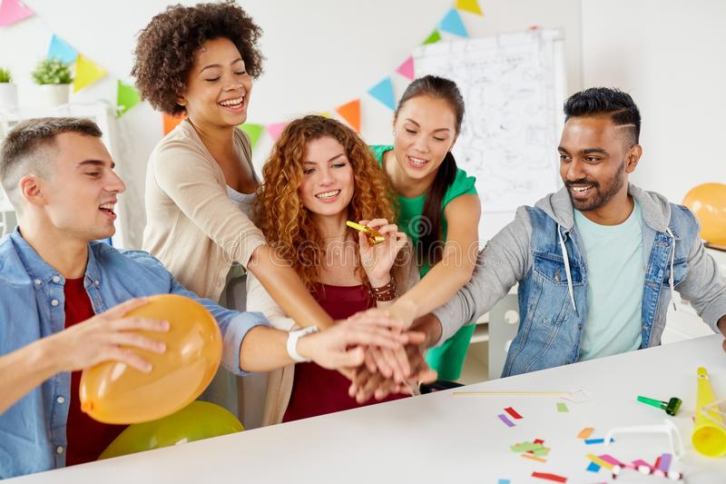 Happy business team at office party holding hands. Teamwork, success and celebration concept - happy business team holding hands together at office corporate royalty free stock image