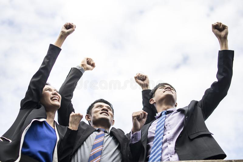 Teamwork and success concept, group of happy business people celebrating and making high hand to sky after achieving the highest stock images