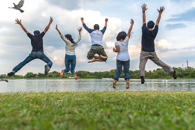Teamwork success concept with group of jumping friends in the public park. stock photography