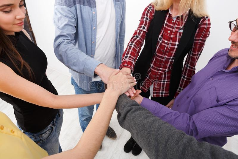 Teamwork and teambuilding, people connect hands. Multiethnic team put hands together, connection, teambuilding and alliance concept. Crop of young people unite stock image