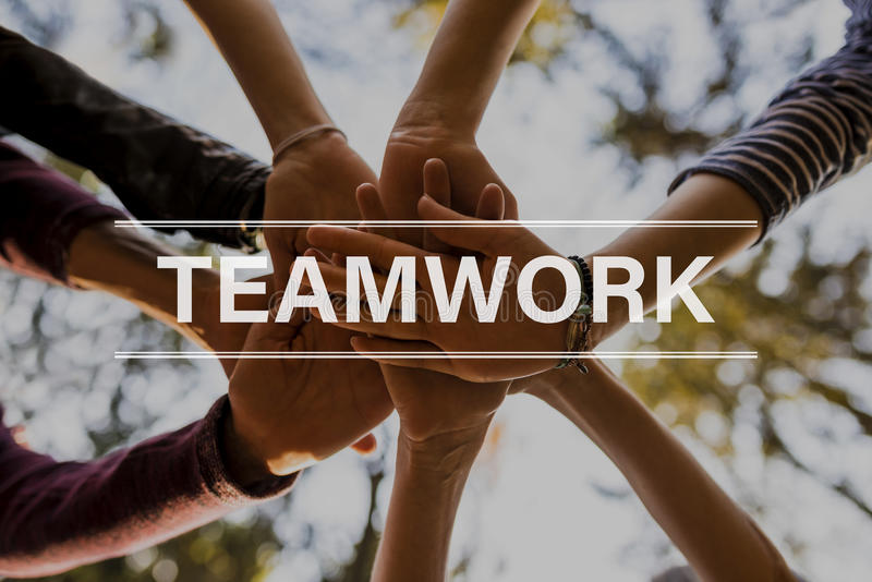 Teamwork text over four people stacking hands. Outside in nature stock photography