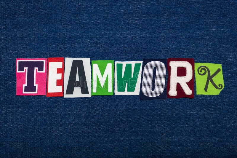 TEAMWORK text word collage, multi colored fabric on blue denim, team effort concept stock photo