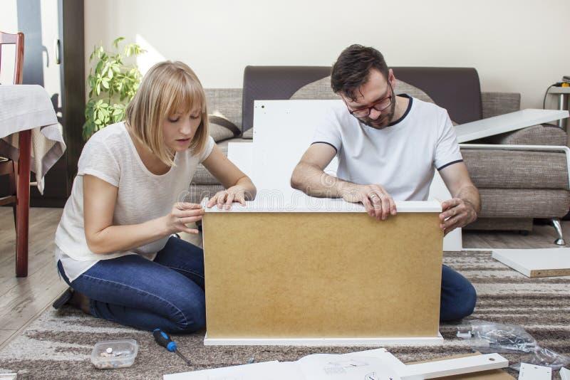 teamwork A torção do marido e da esposa junto a mobília na sala de visitas, combinando os elementos de madeira do grupo da mobíli imagem de stock royalty free