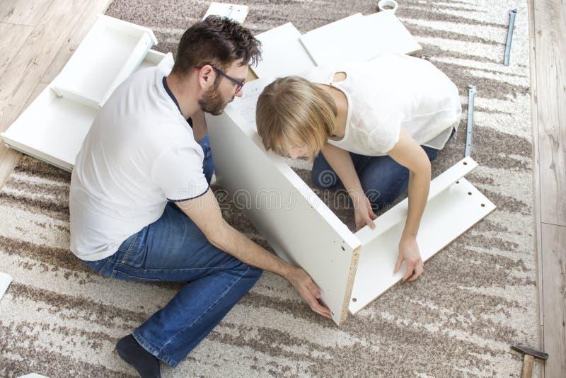 teamwork A torção do marido e da esposa junto a mobília na sala de visitas, combinando os elementos de madeira do grupo da mobíli fotografia de stock royalty free