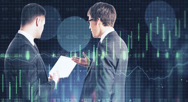 Teamwork and trade concept. Attractive european businessmen with forex chart on blurry dark bokeh background. Teamwork and trade concept. Double exposure stock photo