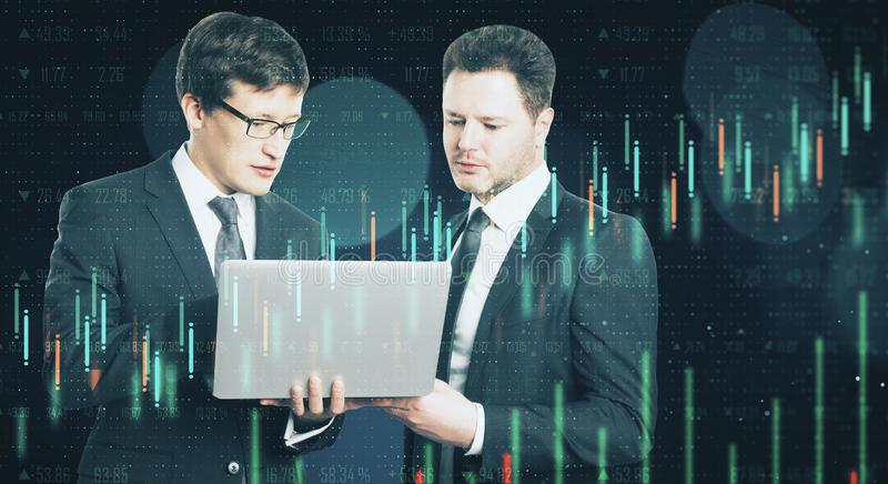 Teamwork and trade concept. Attractive european businessmen using laptop with forex chart on blurry dark bokeh background. Teamwork and trade concept. Double stock images