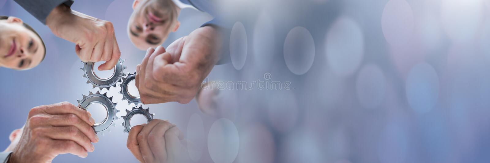 Teamwork transition with business people holding gear cogs stock image
