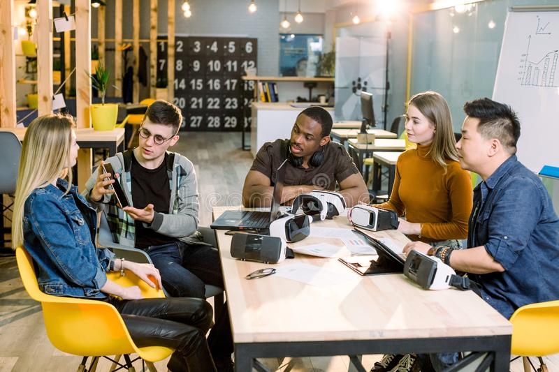 Teamwork trying devices and virtual reality glasses for work in creative office. Five diverse young people using new stock image