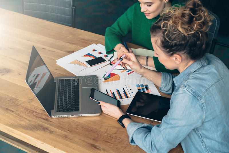 Teamwork. Two young business women sitting at table in front of laptop. On table is tablet computer and paper charts. stock photos