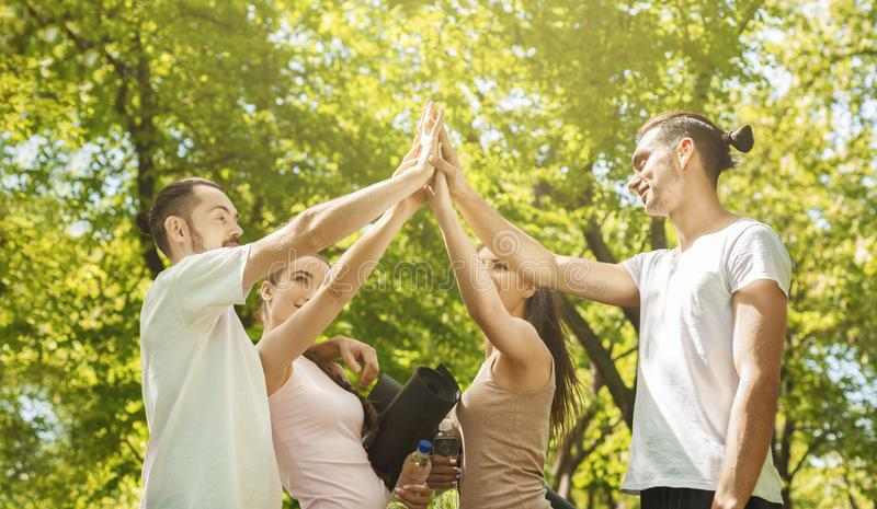 Excited young people giving high five after successful training together stock photography