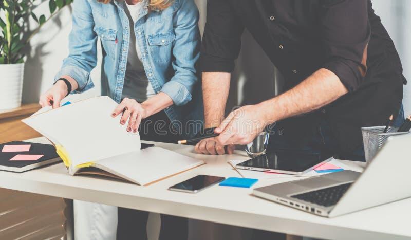 teamwork Uomo d'affari e donna di affari che stanno tavola vicina e sfogliati una cartella con i documenti fotografia stock libera da diritti