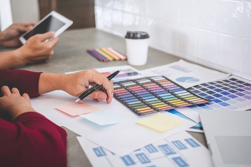 Teamwork von den jungen kreativen Designern, die zusammen an Projekt und Farbmusterproben f?r Auswahlfarbton auf digitalem w?hlen stockbild