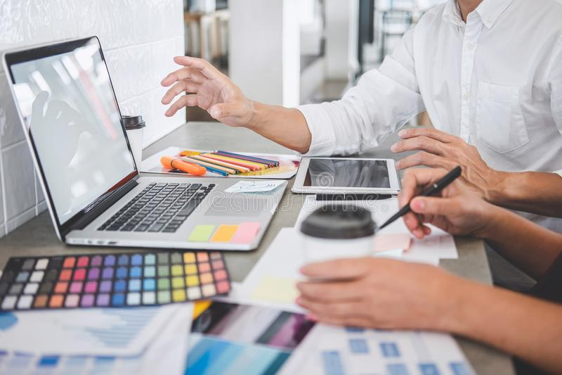 Teamwork von den jungen kreativen Designern, die zusammen an Projekt und Farbmusterproben f?r Auswahlfarbton auf digitalem w?hlen lizenzfreie stockfotografie