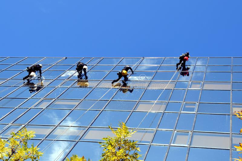 Teamwork - window cleaners at work royalty free stock image