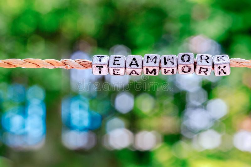 Teamwork word hanging by rope with beautiful green nature bokeh. Background with vintage retro tone. Cooperation, togetherness, partnership concept stock image