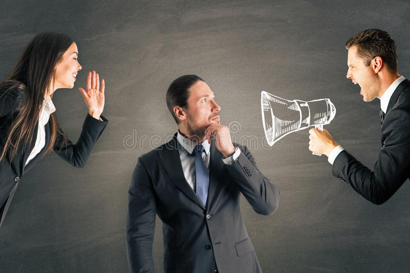 Teamwork and work concept. Businesspeople shouting at young european businessman using speaker. Teamwork and work concept royalty free stock photos