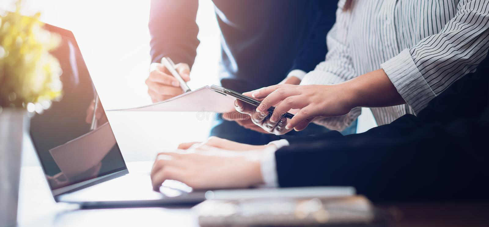 Teamwork working on laptop computer and smartphone in creative office. Successful confident business startup concept. royalty free stock photography