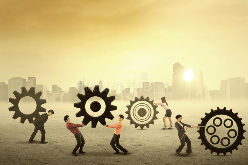 Teamwork works together to build a gear system stock photography