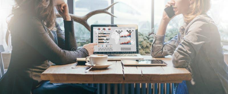 Teamwork, zwei junge Geschäftsfrauen, die über Tabelle von einander sitzen Auf Tabellenlaptop, Kaffeetasse und Tablet-Computer stockbilder