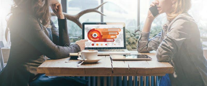 Teamwork, zwei junge Geschäftsfrauen, die über Tabelle von einander sitzen Auf Tabellenlaptop, Kaffeetasse und Tablet-Computer lizenzfreie stockfotografie