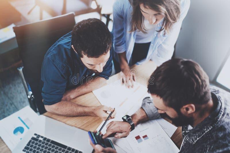 Teamworkarbeteprocess Grupp av unga coworkers som tillsammans arbetar i modern kontorsvind använda för telefon för man mobilt _ fotografering för bildbyråer