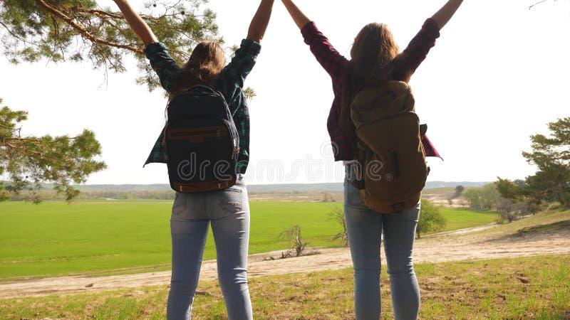 Teamworkfotvandrareflickor som lyfter upp hennes h?nder och att fira Victory And Enjoying Scenery kvinnor p? semesterlopp igenom royaltyfri fotografi