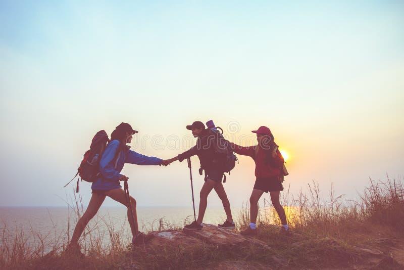 Teamworkfotvandrarekvinnor som hjälper hennes vän, klättrar upp royaltyfri fotografi