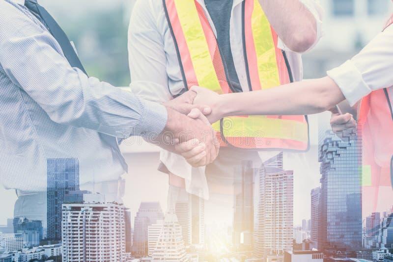 Teamworkprofessionelln av handen för väg-och vattenbyggnadsingenjörbyggmästareskakan sammanfogar funktionsdugligt tillsammans arkivbild