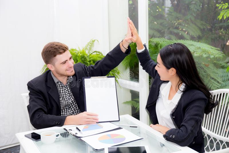 Teamzakenlui hallo vijf wat betreft de handmens en vrouw met glimlachende vergadering voor viering op kantoor stock foto