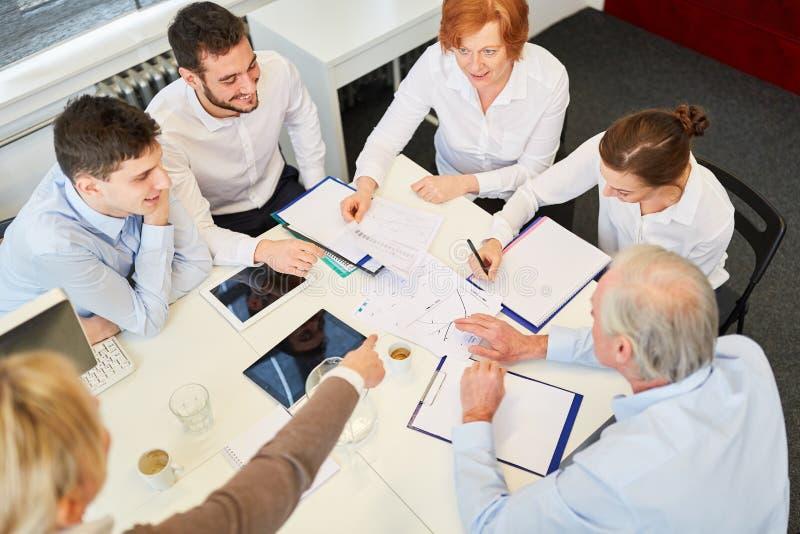 Teamzitting samen in commerciële vergadering stock fotografie