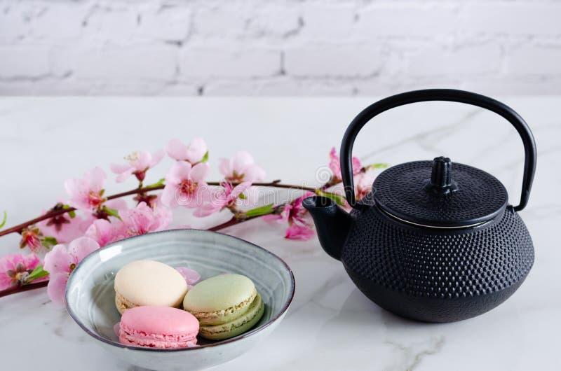 Teapot και macarons με τα λουλούδια άνοιξη στοκ εικόνες