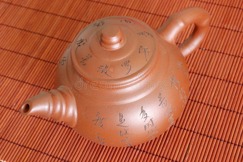 Teapot. Against on bamboo mat royalty free stock image