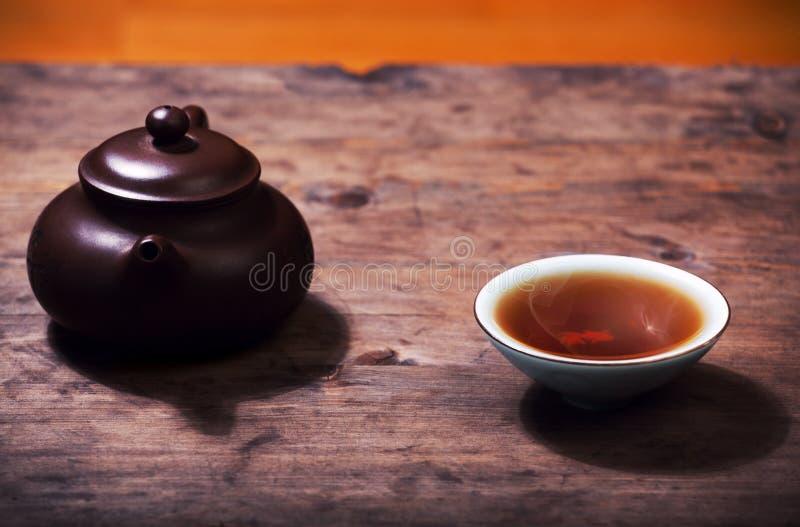 Teapot black hot tea cup wooden desk royalty free stock image