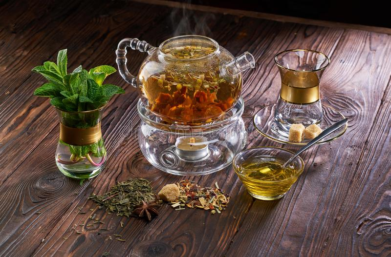Teapot and cup of herbal tea and fresh mint on wooden table royalty free stock photography