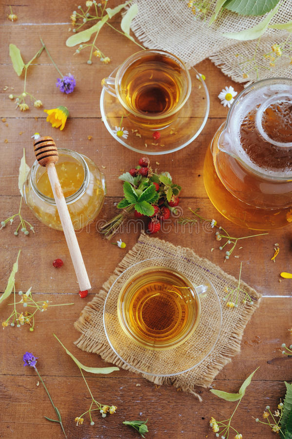 Teapot and cups of herbal tea with linden flowers, lavender and strawberries on wooden table stock image