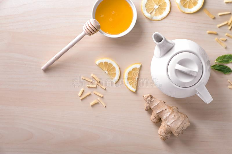 Teapot of delicious tea with ginger, lemon and honey on table royalty free stock photos