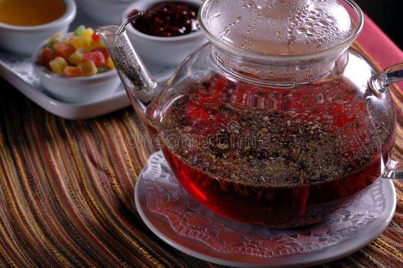 Teapot e copo de vidro com doces fotos de stock
