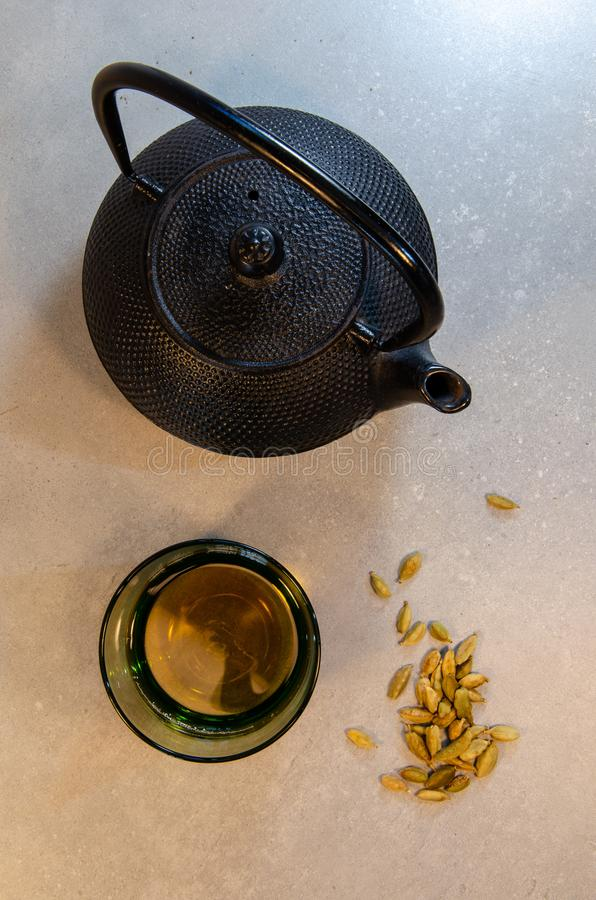 Teapot, glass of tea and cardamom. Teapot, tea in a glass, and cardamom. Neutral background stock images
