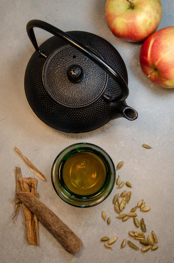 Teapot, glass of tea and cardamom. Teapot, tea in a glass, and cardamom. Neutral background royalty free stock photos