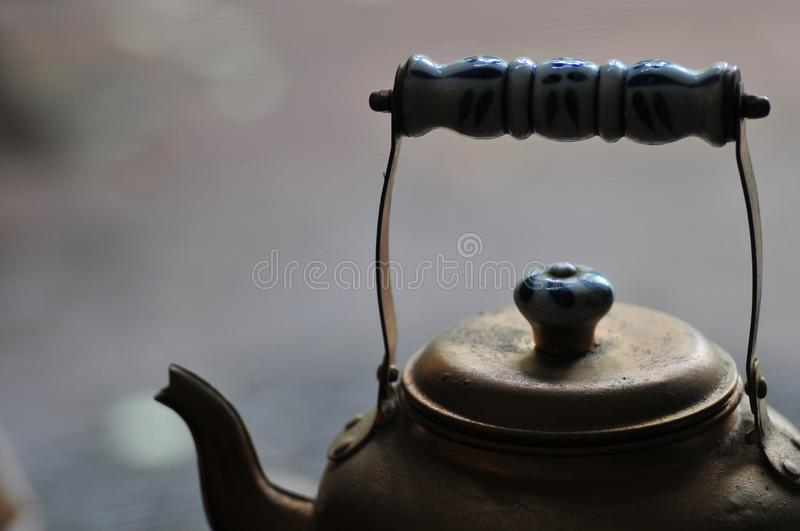 Teapot - Golden Brass Bronze Tea Pot - With Blue and White Enamel Handle Abstract Mood Background stock images